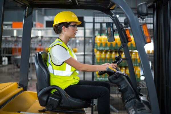 Female factory worker driving forklift in factory